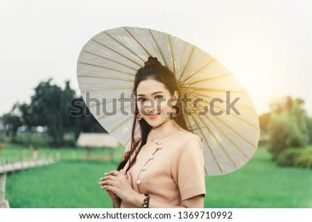 Beautiful Asian woman in local dress holding paper umbrella standing and enjoy natural on bamboo bridge in rice field