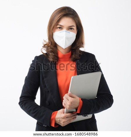 Beautiful Asian woman in suit business dress on white background wearing surgical protect mask holding notebook computer. Concept for prevent for coronavirus outbreak and dirty air pollution.