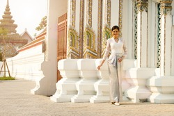 Beautiful Asian Woman in Thai Traditional Costume which is very Elite and old Fashion. Lady in Public area Wat Temple with retro architecture for travel tourism. copy space background