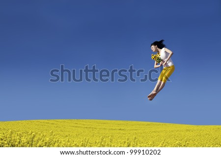 Beautiful asian woman jumping on the canola field with flower