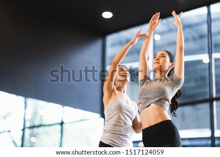 Beautiful Asian woman learning yoga pose with female instructor in yoga studio or health club. Sport exercise activity, gymnastics or ballet dancing class, or healthy people lifestyle concept