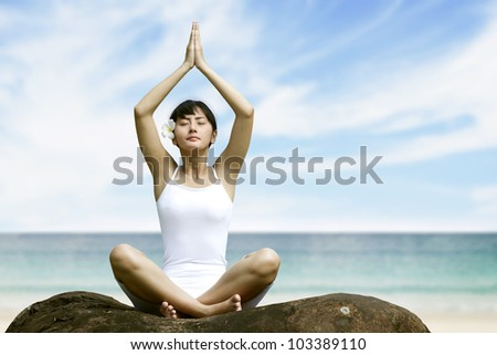 Beautiful asian woman meditating at beach