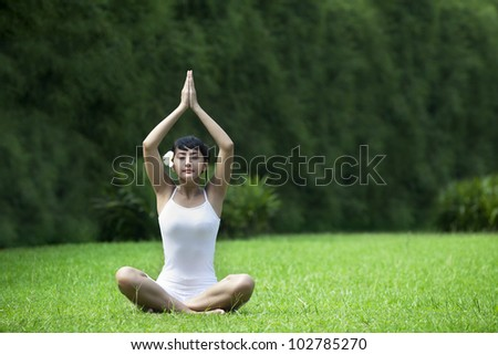 Beautiful Asian Woman meditating on grass. Shot in the garden during summer