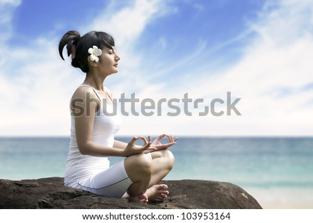 Beautiful asian woman meditating on the beach sitting over a rock