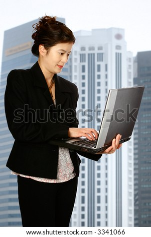 Beautiful Asian woman on her laptop, with corporate skyscrapers in the background.