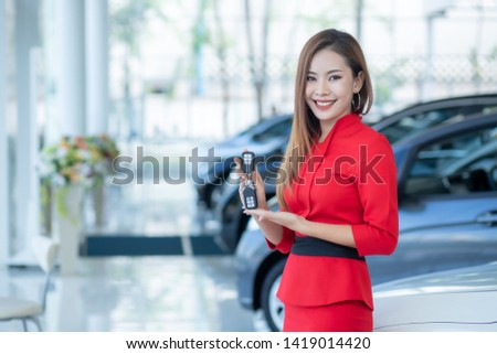 Beautiful Asian woman or car salesman Stand holding a new car remote key in the showroom, Cars For Sale.