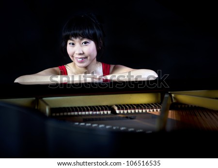 Beautiful Asian woman playing the grand piano - stock photo