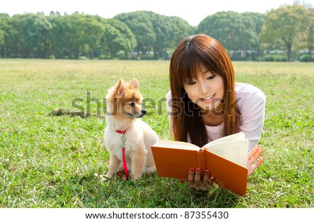 beautiful asian woman reading book with dog in the park