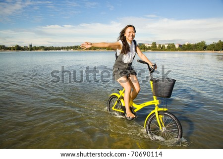 Beautiful asian woman riding a bike in water