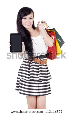 Beautiful asian woman showing empty screen of computer tablet while carrying shopping bags