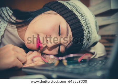 beautiful asian woman sleep on the desk with laptop in the library #645829330