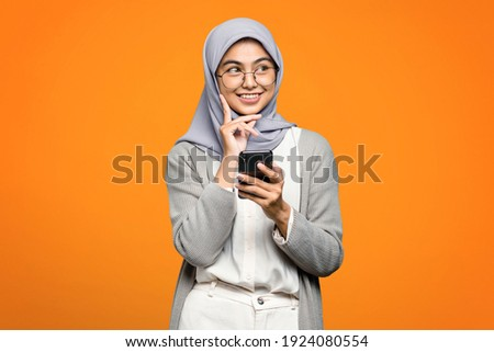 Beautiful Asian woman smiling and holding smartphone