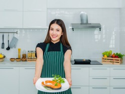 Beautiful Asian woman standing smiling holding dish salmon steak a health breakfast with happiness in the kitchen at home. Lifestyle and healthy concept.