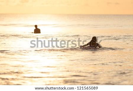 Beautiful asian woman swimming on surfboard