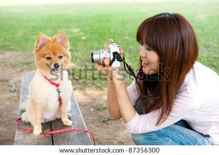 beautiful asian woman taking dog's photo in the park