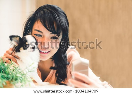 Beautiful Asian woman taking selfie with cute Chihuahua dog at home, with copy space. Lovely human and pet friendship, or modern domestic lifestyle concept