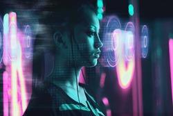 Beautiful asian woman using futuristic computer screen in neon light