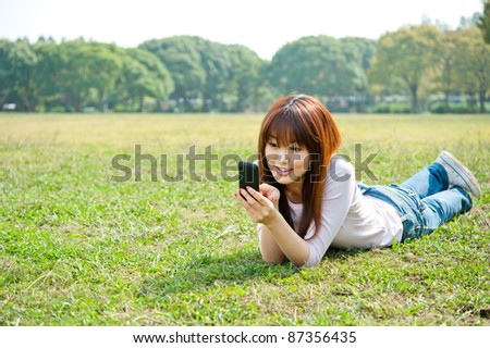 beautiful asian woman using smart phone in the park