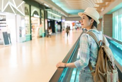 beautiful Asian woman walking around airport. looking window shopping of the duty free shop on the escalator conveyor belt.