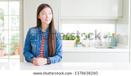 Beautiful Asian woman wearing denim jacket on white table smiling looking side and staring away thinking.