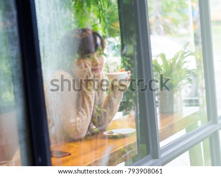 Beautiful Asian woman wearing white sweater and drinking a cup of coffee in glass house cafe, alone, single concept