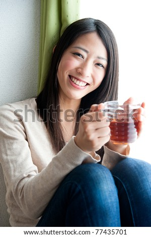 beautiful asian woman with a glass of tea