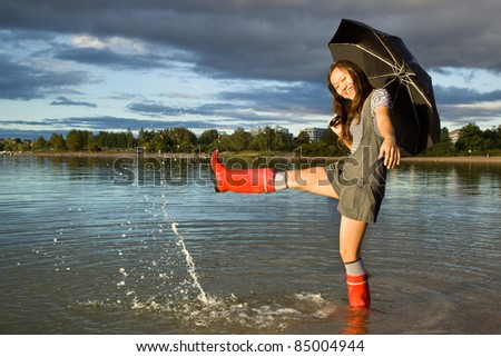 Beautiful asian woman with an umbrella in water