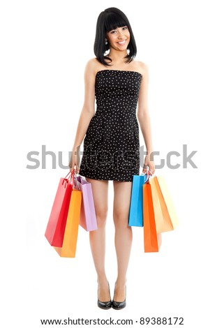 Beautiful asian woman with colored shopping bags isolated on white