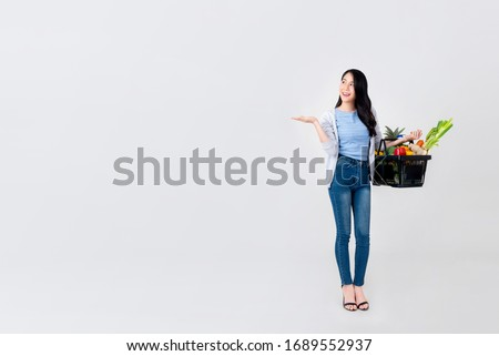 Beautiful Asian woman with open hand holding supermarket shopping basket full of vegetables and groceries isolated on studio light gray background with copy space Foto stock ©