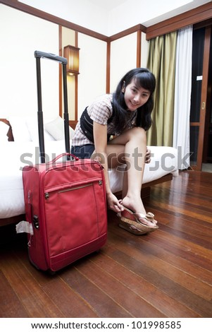 Beautiful Asian woman with suitcase getting ready  in a hotel room - stock photo