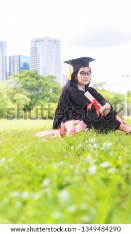 5488b3a092 Beautiful asian women graduating holding diploma with pride and smiling in  an academic gown.Congratulation