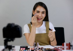 Beautiful Asian women Smiling using eyebrow pencil To show products For online sales Broadcast live through video camera. Concept online shopping sell