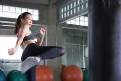 Beautiful Asian young sport  Kickboxing woman exercise kicking bag at the fitness gym. boxer girl punching   real fast kick