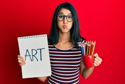 Beautiful asian young woman holding art notebook and colored pencils puffing cheeks with funny face. mouth inflated with air, catching air.