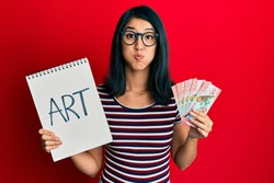 Beautiful asian young woman holding art notebook and 100 new zealand dollars puffing cheeks with funny face. mouth inflated with air, catching air.