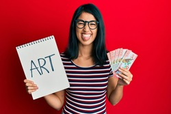 Beautiful asian young woman holding art notebook and 100 new zealand dollars sticking tongue out happy with funny expression.
