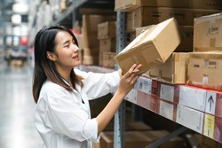 Beautiful Asian young woman looking for goods in warehouse, Logistics concept.