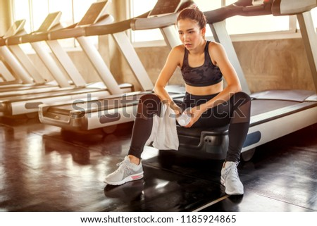 Beautiful Asian young woman tired taking a break from running or exercise sitting on treadmill machine drinking water and towel sweat in fitness gym healthy .girl in sportswear workout rest in morning