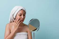 Beautiful Asian young woman touching face and was a feeling of anxiety on her face while looking at the mirror. Skincare and clean concept, Beauty treatment process for rejuvenation.
