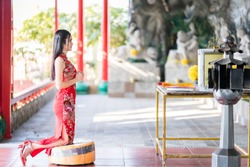 beautiful Asian young woman wearing red traditional Chinese cheongsam decoration sitting for pray to buddha statue for Chinese New Year Festival at Chinese shrine in Thailand