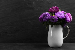 Beautiful asters in jug on table against black background, space for text. Autumn flowers