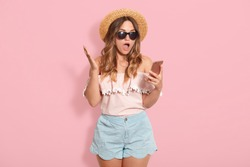 Beautiful astonished woman wearing blouse with bared shoulders, short, straw hat and sunglasses, holding smart phone in hand and posing with open mouth, recives shocking messages from friend.