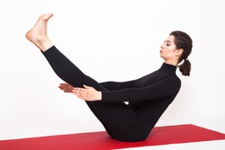 Beautiful athletic girl in black suit doing yoga. naukasana asana - boat pose. Isolated on white background.