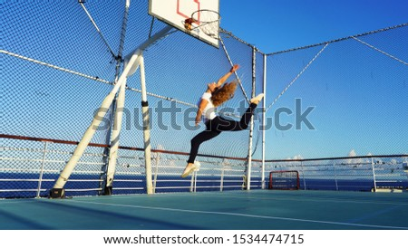 beautiful athletic girl on a basketball court jumps in twine to the basket. red-haired curly model jumping gymnastic elements on the playground