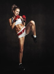 Beautiful athletic girl with boxing gloves hit high foot. Grunge background