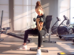 Beautiful athletic muscular woman pumps up the muscles by one arm lifts dumbbell exercise on bench in fitness gym. Young sport girl gains strong muscles physical by weight lifted in fitness studio.