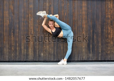 Beautiful athletic young girl gymnast in sportswear, working out, element of gymnastics, doing the splits. wooden and concrete background. Sport motivation, copy space, banner for advertising.