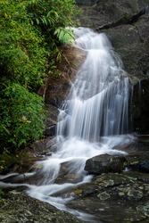 Beautiful Atlantic Rainforest waterfall on green landscape in Tijuca Forest Park, Rio de Janeiro, Brazil