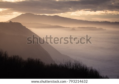 beautiful atmospheric landscape view in sunset on atlantic coastline with huge waves, basque country, france