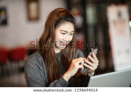 Beautiful Attractive Asian business woman holding smartphone for using social media in coffee shop cafe smile and happiness #1198694014